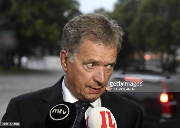 President of Finland Sauli Niinisto speaks to journalists as he arrives for the prayer service at the Turku Cathedral for the victims of Friday's...