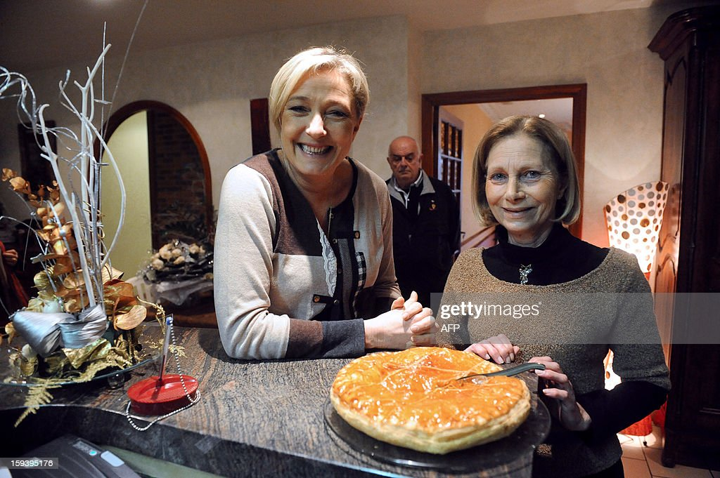 President of French far-right party Front national (FN), Marine Le Pen (L) poses in front of an Epiphany cake, on January 13, 2013 in Laboutarie, a French southwestern village, following a press conference focused on Paris' march which gather thousands people protesting against same-sex marriage, as part of a meeting with local FN supporters. AFP PHOTO/REMY GABALDA