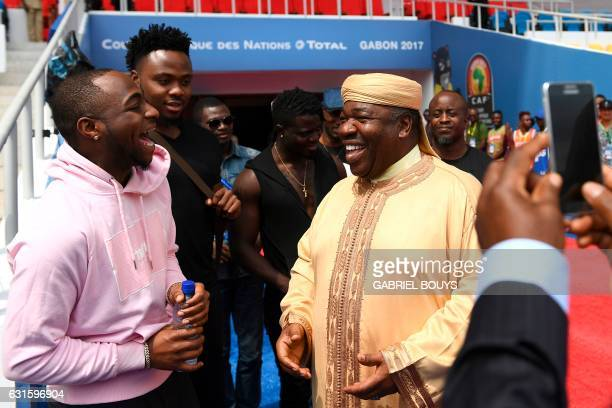 President of Gabon Ali Bongo Ondimba jokes with Americanborn Nigerian recording artist Davido during a visit at the Stade de lAmitié Sinogabonaise...