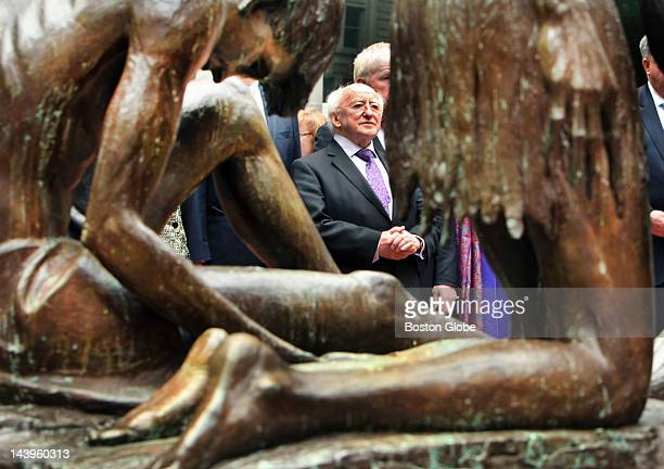 President of Ireland Michael Higgins visited the Boston Irish Famine Memorial in downtown Boston He is framed through one of the statues during the...