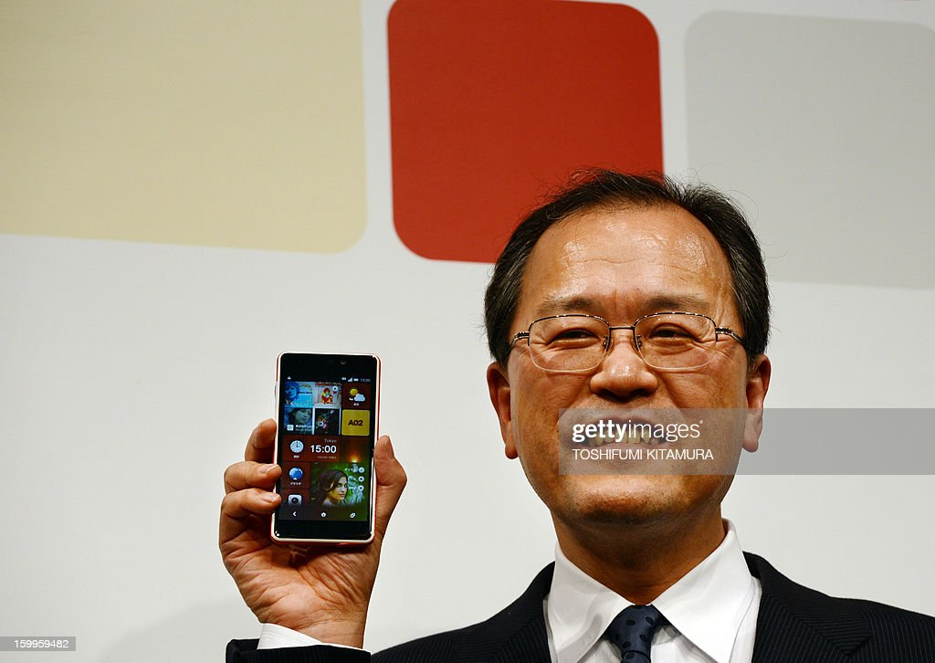 President of Japanese telecom operator KDDI, Koji Tanaka, poses with the company's latest smartphone, the 'INFOBAR A02', during a press preview in Tokyo on January 24, 2013. Japan's mobile carrier KDDI will start selling the Naoto Fukasawa and Yugo Nakamura-designed smartphones from mid-February.