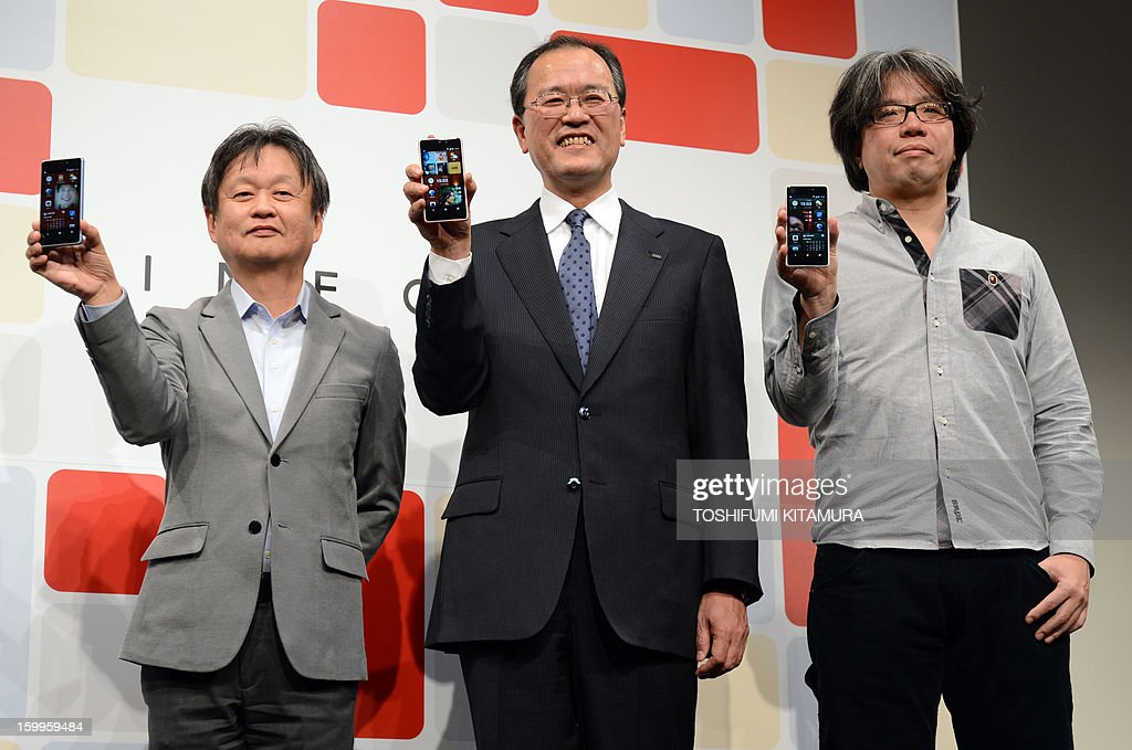 President of Japanese telecom operator KDDI, Koji Tanaka (C), poses with designers Naoto Fukasawa (L) and Yugo Nakamura (R) to promote the company's latest smartphone, the 'INFOBAR A02', during a press preview in Tokyo on January 24, 2013. Japan's mobile carrier KDDI will start selling the Naoto Fukasawa and Yugo Nakamura-designed smartphones from mid-February.