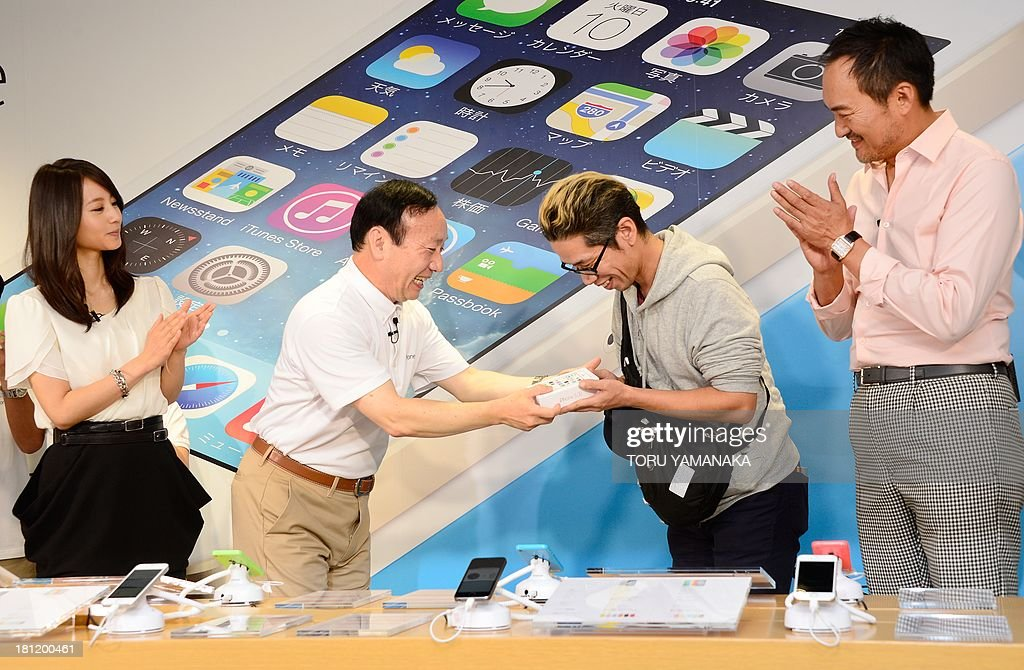 President of Japan's biggest mobile carrier NTT Docomo Kaoru Kato (2nd L) hands an iPhone box to the first customer, Hidenori Sato (2nd R) of Apple's new iPhone 5s as Japanese actor Ken Watanabe (R), actress Maki Horikita (L) applaud at a Docomo shop in Tokyo on September 20, 2013. Apple's new iPhone 5s and 'cheap' 5C models on September 20 went on sale in Japan. AFP PHOTO/Toru YAMANAKA