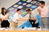 President of Japan's biggest mobile carrier NTT Docomo Kaoru Kato hands an iPhone box to the first customer Hidenori Sato of Apple's new iPhone 5s as...