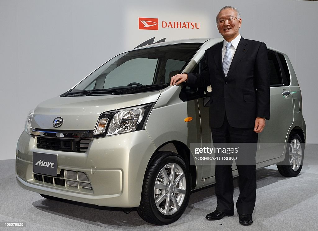 President of Japan's mini car maker and Toyota subsidiary Daihatsu, Koichi Ina, poses as he introduces the company's new car called 'Move' in Tokyo on December 20, 2012. The new model Move has economy efficient 660cc engine that achieves 29 kpl and a crash prevention brake system. AFP PHOTO / Yoshikazu TSUNO