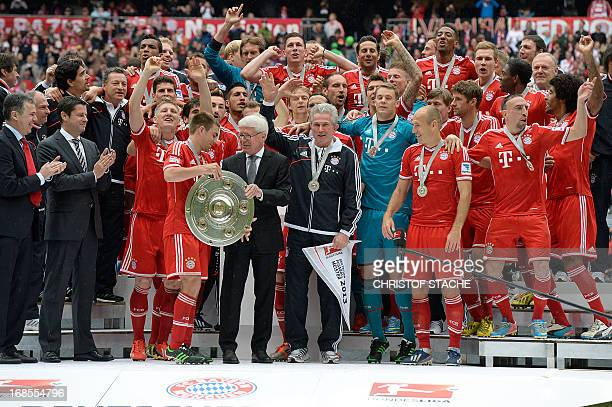 President of last year's champion Borussia Dortmund Reinhard Rauball gives the German football league champion's trophy to Bayern Munich's defender...