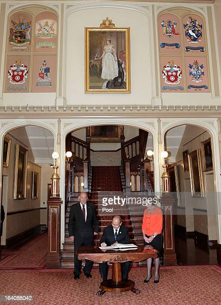 President of Myanmar Thein Sein signs a visitors' book as Marie Bashir Governor of New South Wales and her husband Sir Nicholas Shehadie look on at...