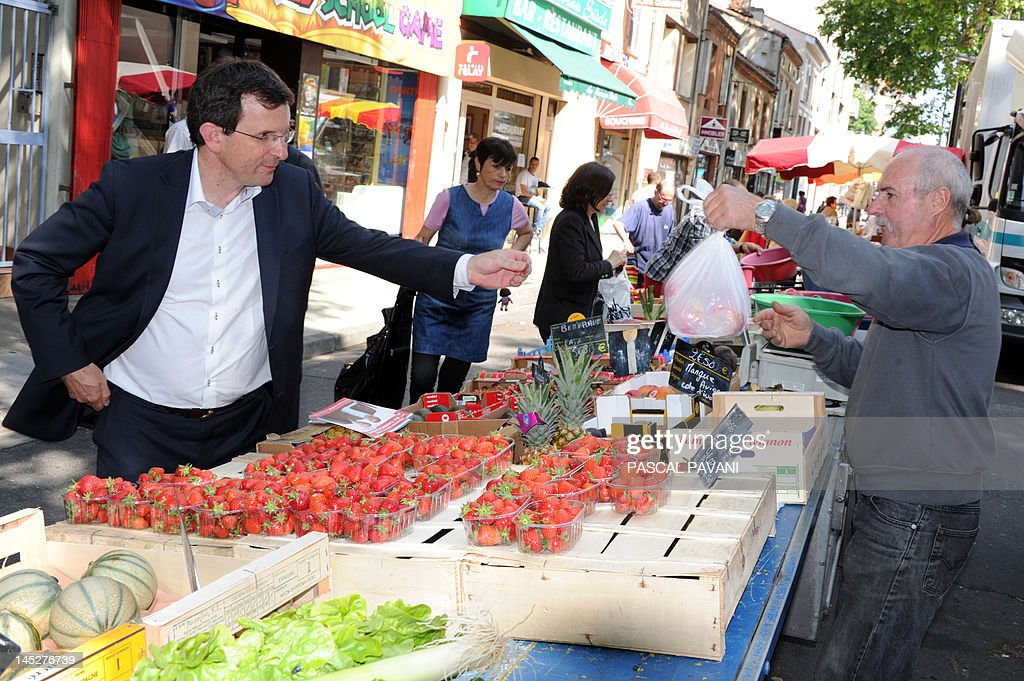 President of National Union of Students of France - Independent and Democratic (UNEF-ID) and Socialist Party (PS) candidate in the 9th constituency of Haute-Garonne for French parliamentary election, Christophe Borgel (L), buys fruits from a vendor as he meets with inhabitants on a market on May 25, 2012 in Toulouse, southwestern France, as part of his campaign. AFP PHOTO / PASCAL PAVANI