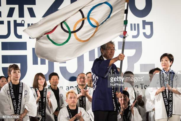 President of Olympic Committee Tsunekazu Takeda waves an Olympic flag applauded by Japanese athletes during the Tokyo 2020 flag tour festival for the...