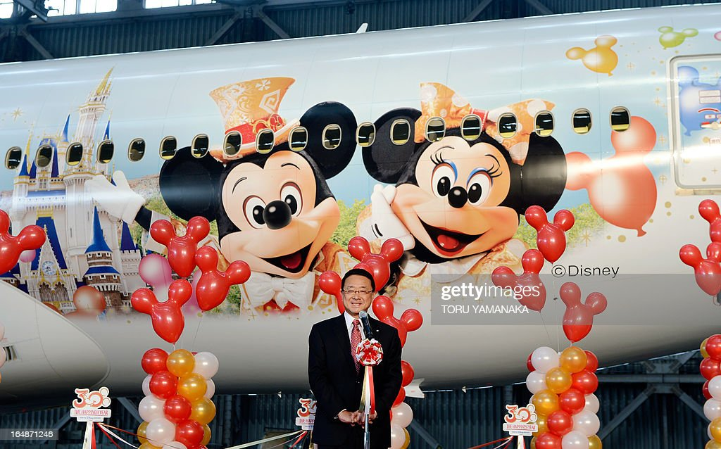 President of Oriental Land, the operator of the Tokyo Disneyland and Disney Sea theme parks, Kyoichiro Uenishi (C) delivers a speech in front of a Boeing 777-200 plane decorated with Disney characters at a hangar of Japan Airlines (JAL) of Haneda Airport in Tokyo on March 29, 2013. JAL unveiled the special plane for domestic flights on March 29, ahead of the 30th anniversary of the Tokyo Disneyland on April 15. AFP PHOTO / Toru YAMANAKA