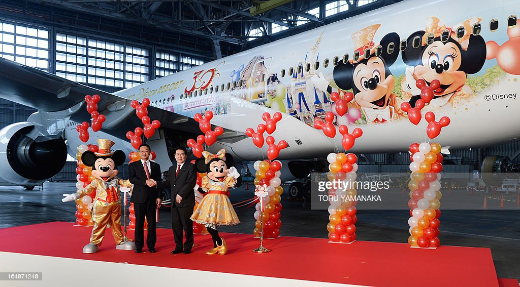 President of Oriental Land, the operator of the Tokyo Disneyland and DisneySea theme parks, Kyoichiro Uenishi (2nd L) shakes hands with President of Japan Airlines (JAL) Yoshiharu Ueki (2nd R) next to Mickey Mouse (L) and Minnie Mouse (R) mascots in front of a Boeing 777-200 decorated with Disney characters at a JAL hangar of Haneda Airport in Tokyo on March 29, 2013. JAL unveiled the special plane for domestic flights on March 29, ahead of the 30th anniversary of the Tokyo Disneyland on April 15. AFP PHOTO / Toru YAMANAKA