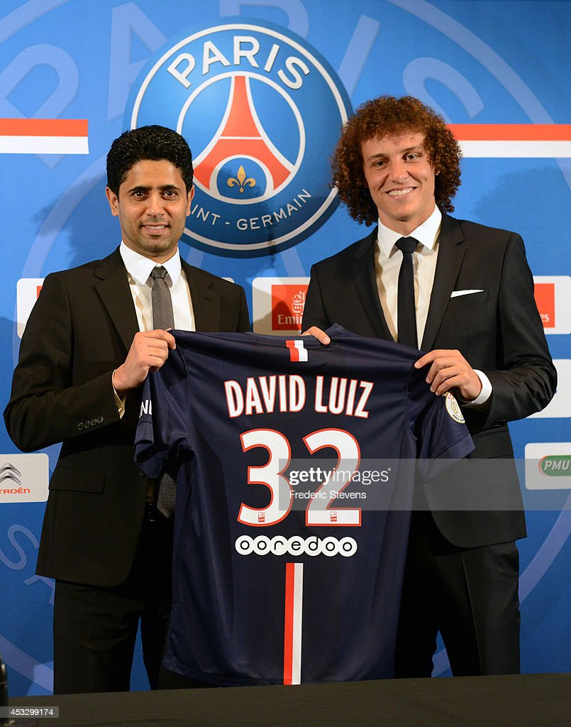 President of PSG Nasser Al-Khelaifi (L) presents to David Luiz (R) his new jersey (#32) during the Brazilian official presentation after signing for PSG at The Peninsula Hotel on August 7, 2014 in Paris, France.