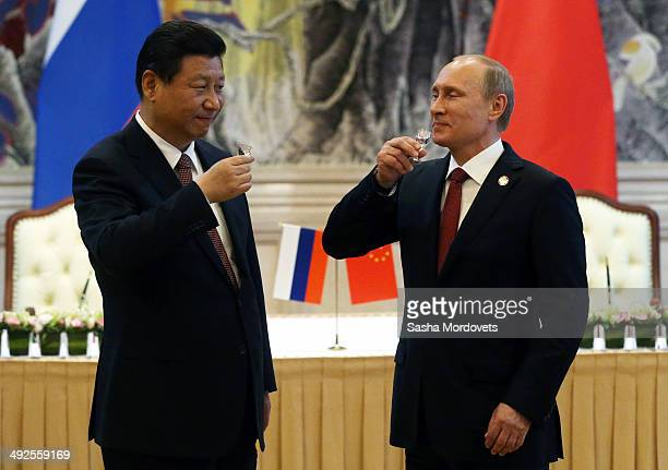 President of Russia Vladimir Putin and Chinese President Xi Jinping toast with vodka during a signing ceremony on May 21 2014 in Shanghai China...