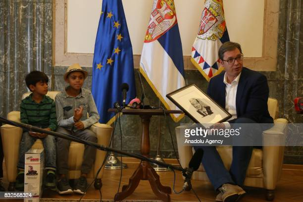 President of Serbia Aleksandar Vucic holds a gift in his hands which is a portrait of him made by an Afghan refugee child Farhud Nuri during an aid...