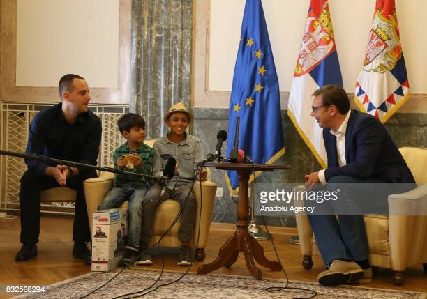 President of Serbia Aleksandar Vucic meets with an Afghan refugee child Farhud Nuri and his family during an aid campaign in Belgrade Serbia on...