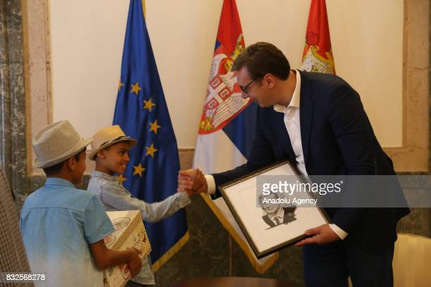 President of Serbia Aleksandar Vucic receives a gift which is a portrait of him made by an Afghan refugee child Farhud Nuri during an aid campaign in...