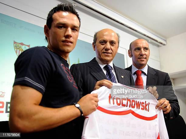 President of Sevilla's football club Jose Maria del Nido poses with Sevilla's new German midfield Piotr Trochowski and Sevilla's deputy sports...