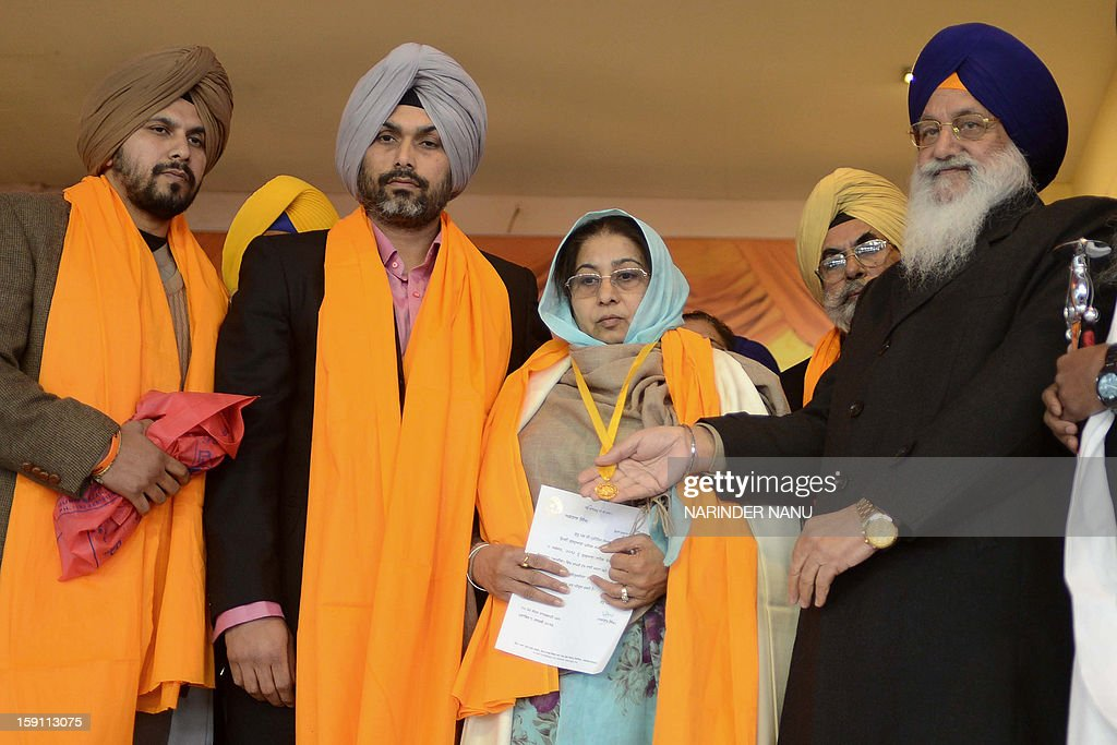 President of Shiromani Gurdwara Parbandhak Committee (SGPC), Avtar Singh Makkar (R) presents a gold medal to Satpal Kaleka, (C) the wife of the late Satwant Singh Kaleka who was killed by a gunman at a Sikh Shrine in Wisconsin in the United States, and her sons Pardeep Singh (2L) and Amardeep Singh (L) at the Sikh Shrine Golden temple complex in Amritsar on January 8, 2013. A gunman on August 5 ,2012 shot worshippers at a suburban Sikh temple in Wisconsin in the mid-western United States, killing at least six people before he was shot dead by police.