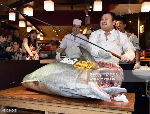President of sushi restaurant chain SushiZanmai Kiyoshi Kimura displays a long fish knife as he cuts a 180 kilo giant bluefin tuna at his main...