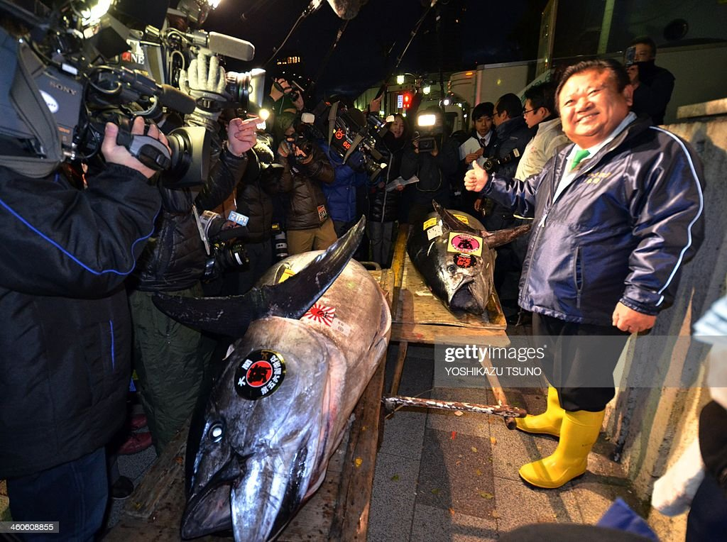 President of sushi restaurant chain Sushi-Zanmai, Kiyoshi Kimura (R), poses next to a 230kg bluefin tuna in front of Tokyo's Tsukiji fish market on January 5, 2014. The bluefin tuna was traded at 70,000 USD (7.36 million yen) at the wholesale market. AFP PHOTO / Yoshikazu TSUNO