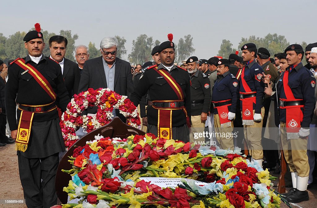 President of the Awami National Party Asfandyar Wali Khan (4th L) places flowers in front of the coffin of Bashir Bilour, the number two to the chief minister of the province, during a funeral ceremony in Peshawar on December 23, 2012. Bilour was killed on December 22 when a suicide bomber stuck when around 100 people including the provincial leadership of the Awami National Party (ANP) had gathered, killing him and eight other people in northwest Pakistan, officials said, in an attack claimed by the Taliban.