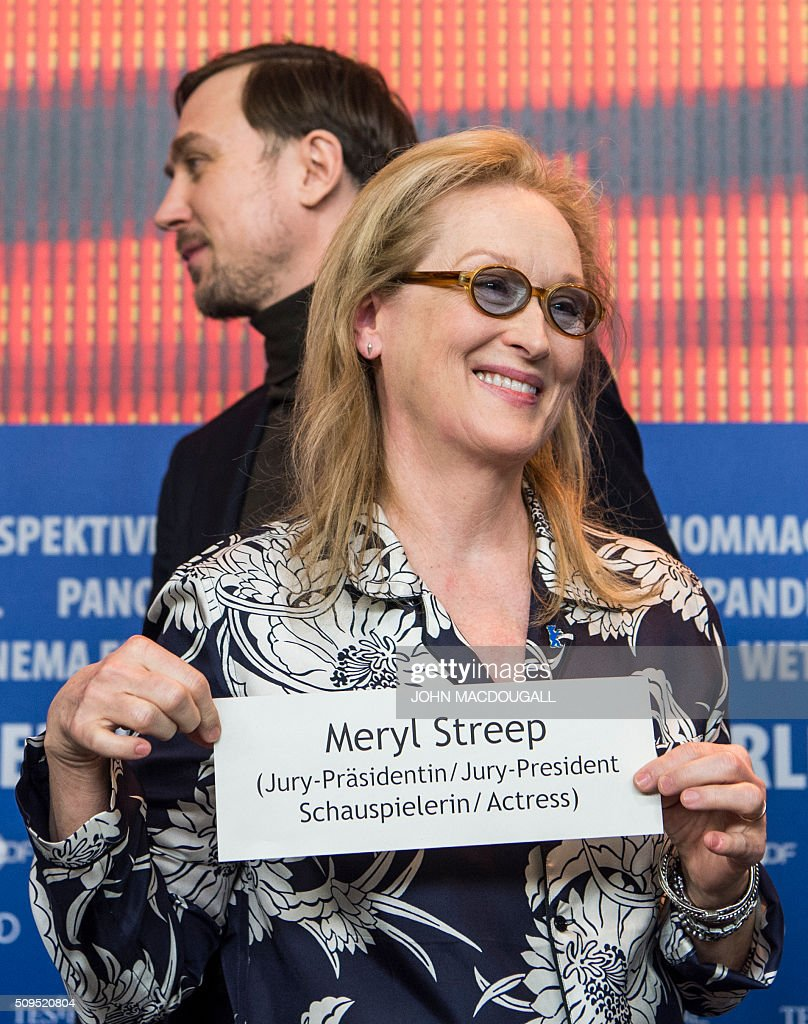 President of the Berlinale Film Festival jury Meryl Streep (front) holds up her name plate in front of German actor and jury member Lars Eidinger at the end of a press conference in Berlin on February 11, 2016. The 66th Berlin film festival starts on February 11, 2016 with a spotlight on Europe's refugee crisis. / AFP / John MACDOUGALL