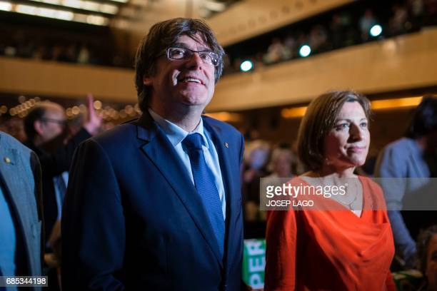 President of the Catalan government Carles Puigdemont smiles beside president of the Catalan parliament Carme Forcadell as they attend a political...