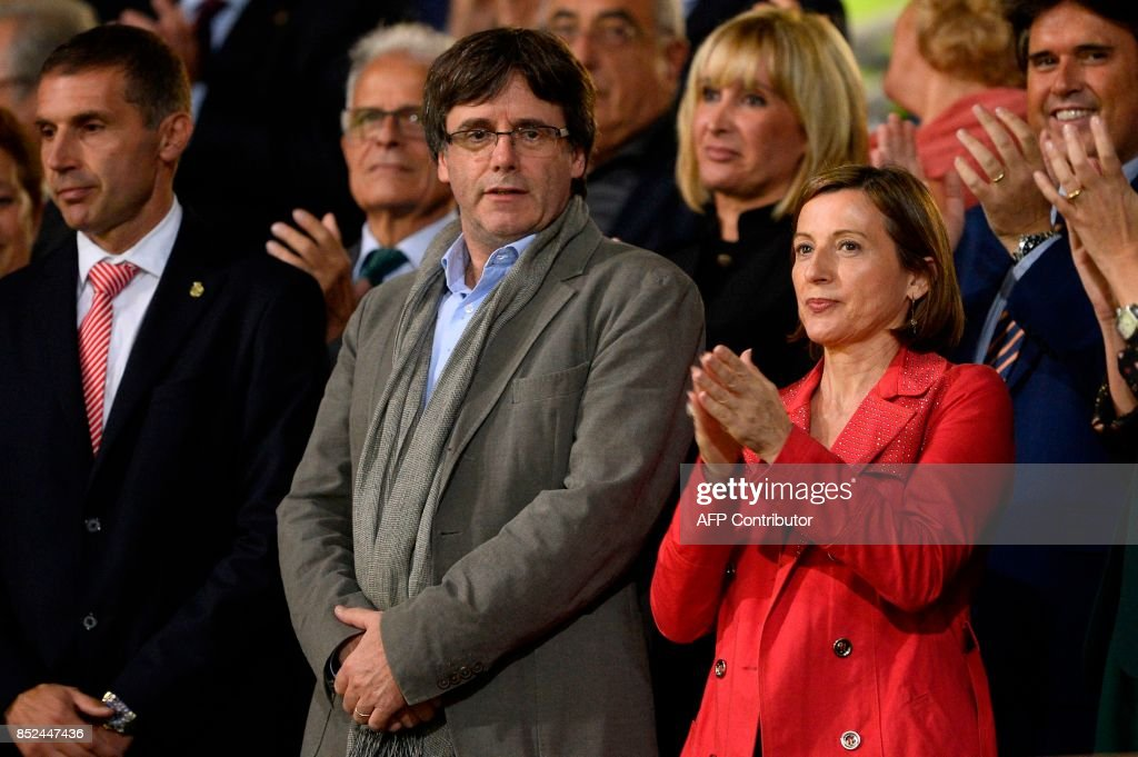 President of the Catalan Government Carles Puigdemont (L) stands past president of the Catalan parliament Carme Forcadell as they wait for the Spanish league football match Girona FC vs FC Barcelona at the Montilivi stadium in Girona on September 23, 2017. / AFP PHOTO / Josep LAGO