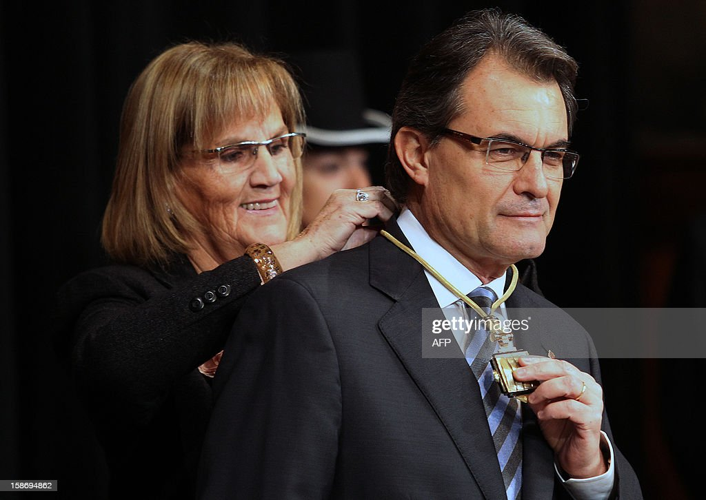 President of the Catalan Parliament Nuria de Gispert (L) ties the medal of the Catalan Presidency around the neck of Catalonia's president Artur Mas during the swearing-in ceremony in Barcelona on December 24, 2012. AFP PHOTO / QUIQUE GARCIA