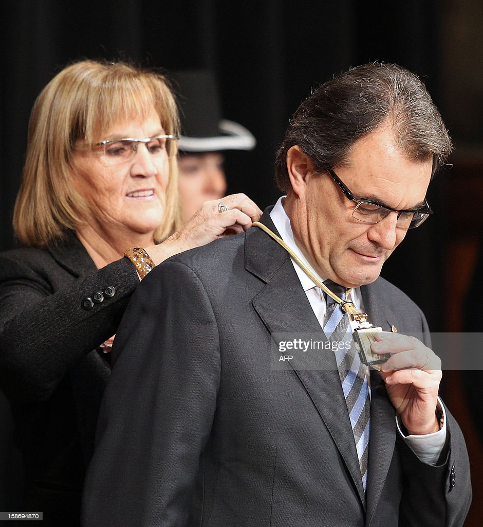 President of the Catalan Parliament Nuria de Gispert (L) ties the medal of the Catalan Presidency around the neck of Catalonia's president Artur Mas during the swearing-in ceremony in Barcelona on December 24, 2012.