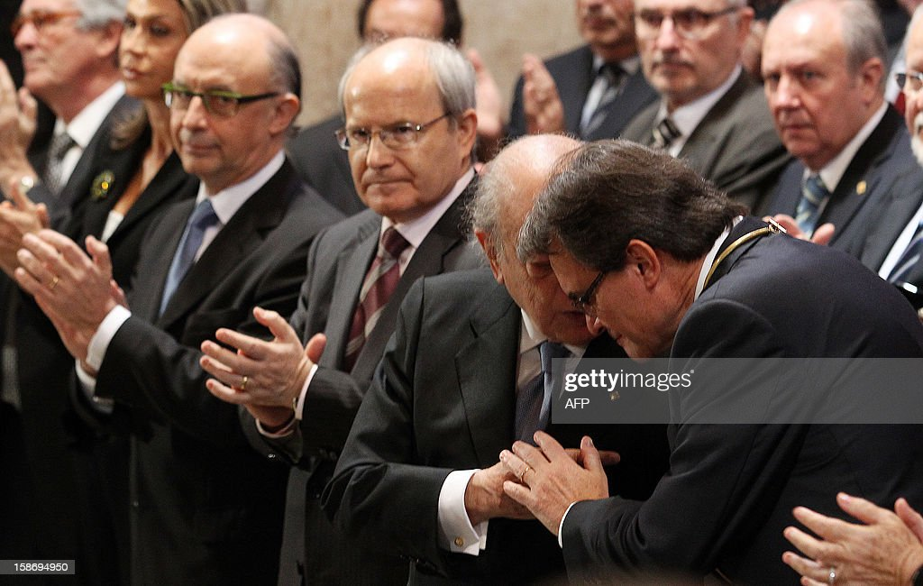 President of the Catalan regional government Artur Mas (R) listens to former Catalan president Jordi Pujol (2nd R) during the swearing-in ceremony in Barcelona on December 24, 2012.