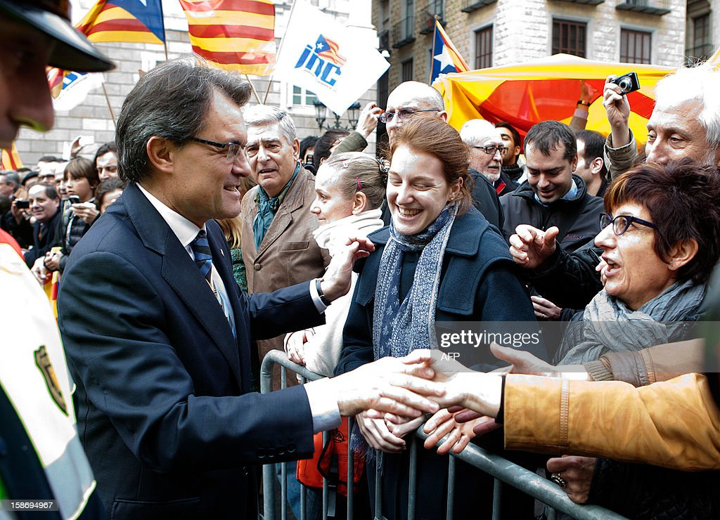 President of the Catalan regional government Artur Mas (L) shakes hands with his supporters after his swearing-in ceremony in Barcelona on December 24, 2012.