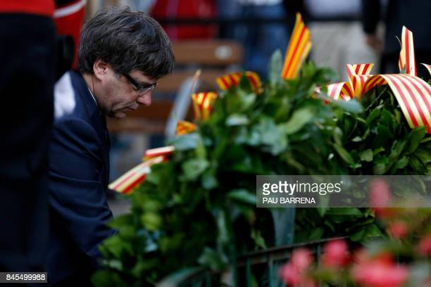President of the Catalan regional government Carles Puigdemont lays a wreath during a ceremony at the Rafael de Casanovas monument in Barcelona on...