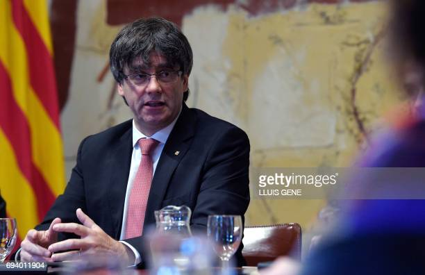 President of the Catalan reional government Carles Puigdemont speaks with his cabinet's members during a meeting prior to publicly announcing the...