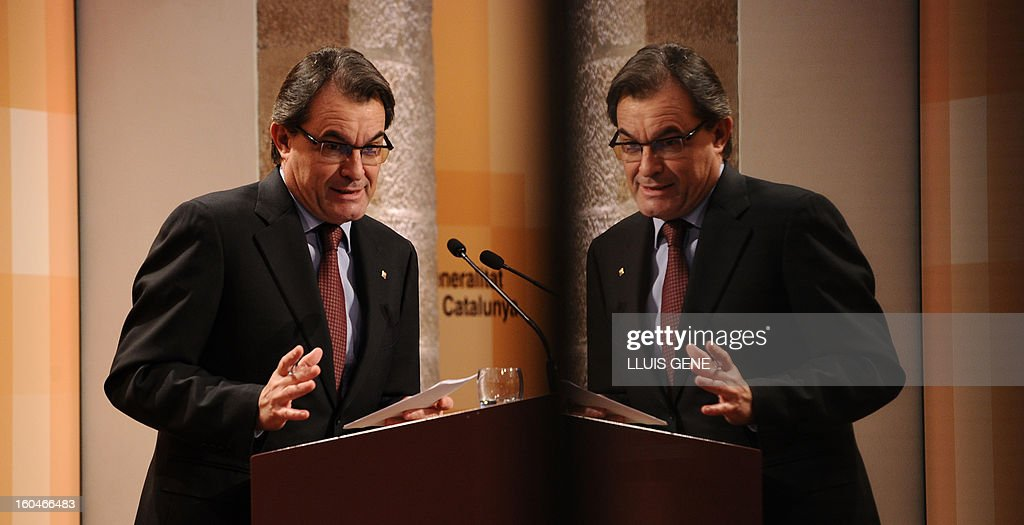 President of the Catalonia regional government and leader of the Catalan party CIU (Convergence and Unity party) Artur Mas, reflected in a window, gives a press conference in Barcelona on February 1, 2013. AFP PHOTO/ LLUIS GENE.