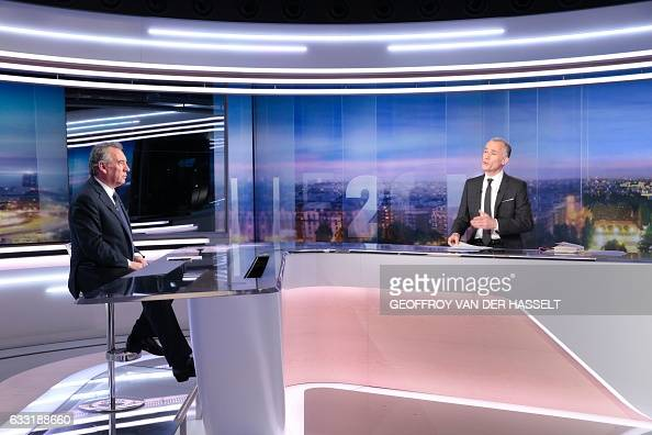 President of the centerright Modem party Francois Bayrou seats in front to French journalist Gilles Bouleau prior to a broadcast interview on a set...
