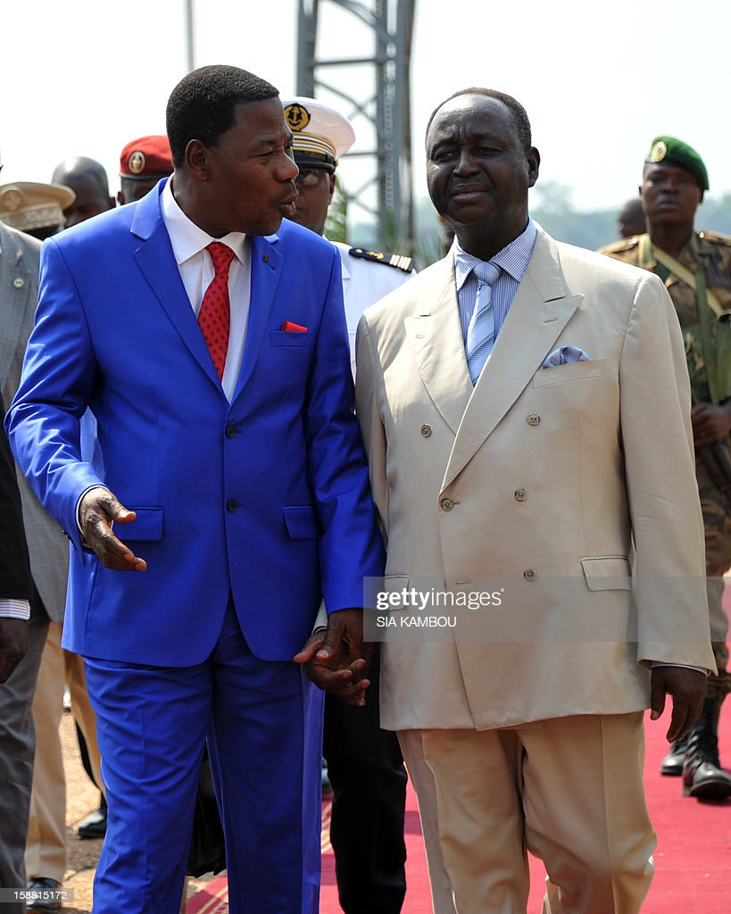 President of the Central African Republic Francois Bozize (R) greets the current president of the African Union and President of Benin Yayi Boni at the airport in Bangui, on December 30, 2012. Rebels in the Central African Republic who have advanced towards the capital Bangui warned they could enter the city even as the head of the African Union prepared to launch peace negotiations. Central African President Francois Bozize also stated today he was open to a national unity government after talks with rebel leaders and that he would not run for president in 2016. AFP PHOTO/ SIA KAMBOU