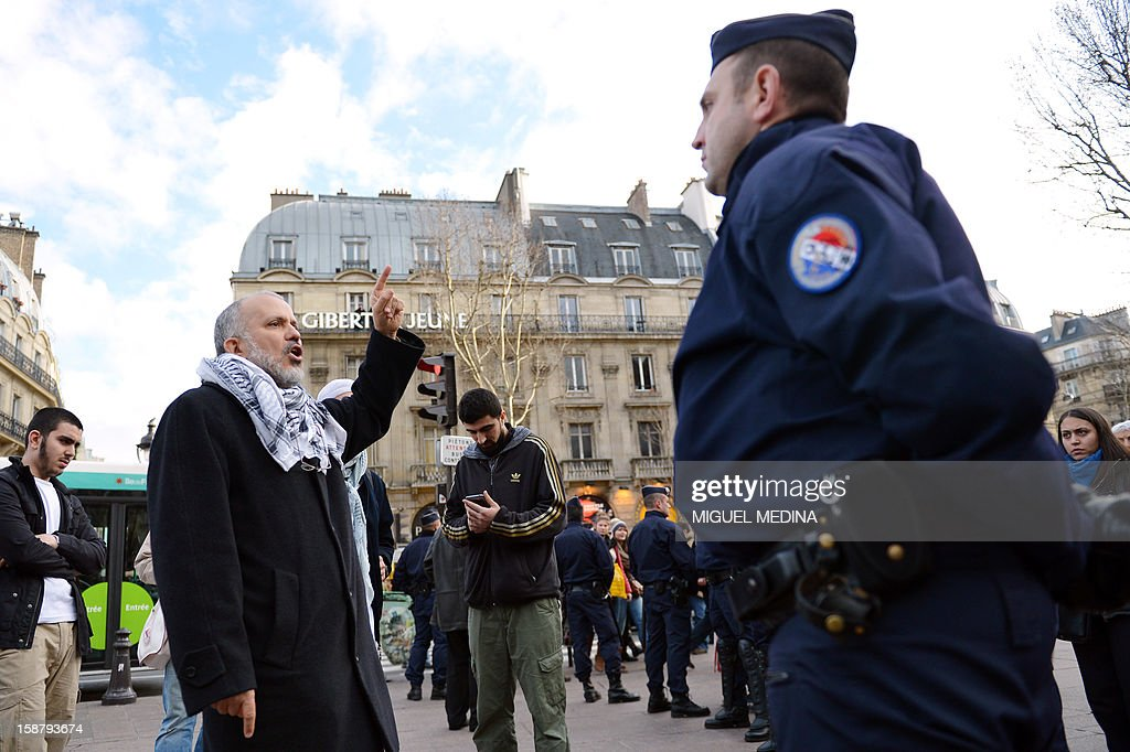 President of the Cheikh Yassine collective Abdelhakim Sefrioui (2ndL) gestures in front of French anti-riot gendarmes during an unauthorized protest to support Palestine, on December 29, 2012 in Paris.