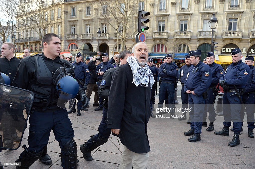 President of the Cheikh Yassine collective Abdelhakim Sefrioui (C) is arrested by French anti-riot gendarmes while taking part in a unauthorized protest to support Palestine, on December 29, 2012 in Paris.