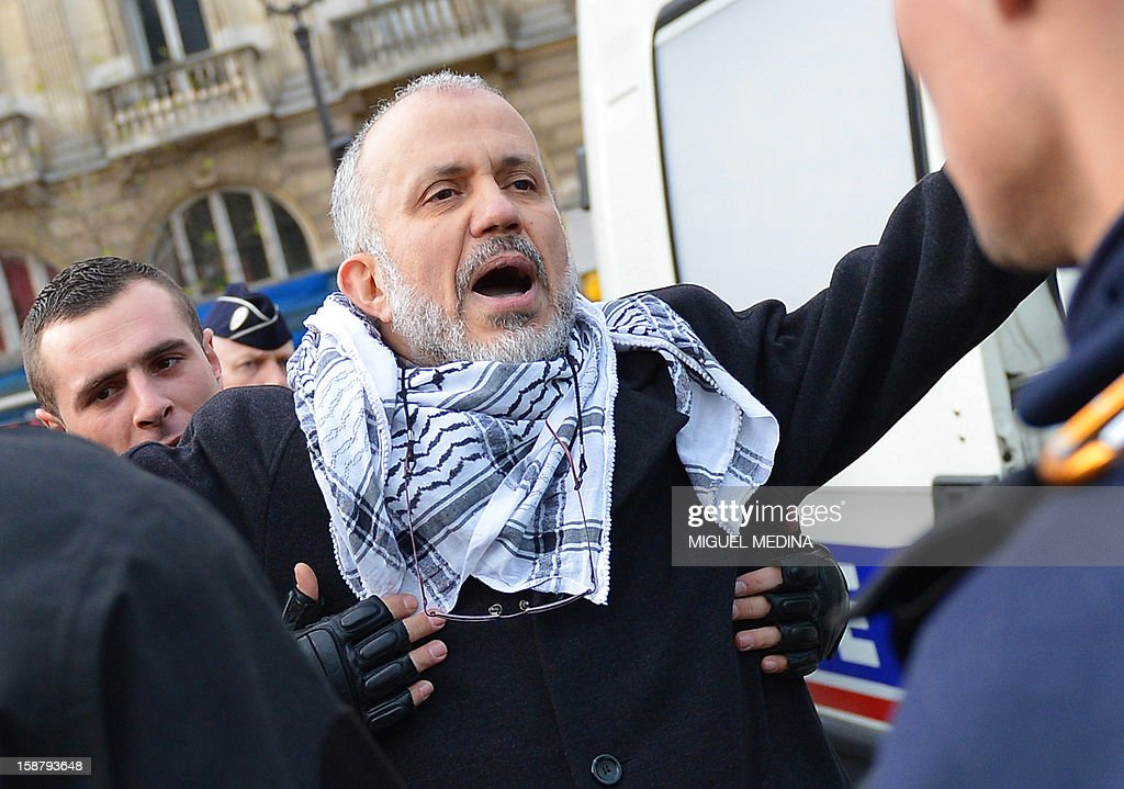 President of the Cheikh Yassine collective Abdelhakim Sefrioui (c) is checked while being arrested by French anti-riot gendarmes after a unauthorized protest to support Palestine, on December 29, 2012 in Paris. AFP PHOTO MIGUEL MEDINA
