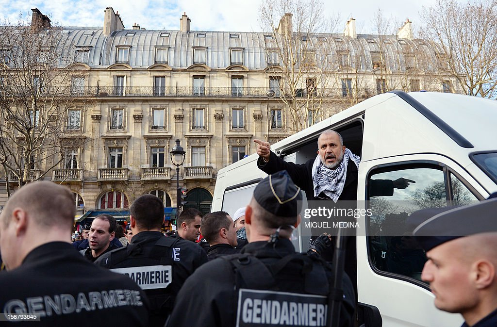 President of the Cheikh Yassine collective Abdelhakim Sefrioui (2ndR) gestures while being arrested by French anti-riot gendarmes after a unauthorized protest to support Palestine, on December 29, 2012 in Paris. AFP PHOTO MIGUEL MEDINA