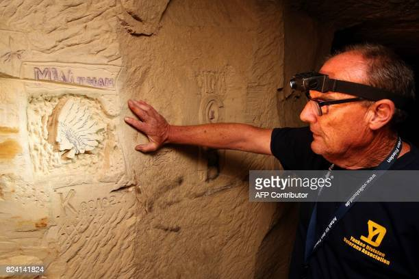 President of the Chemin des Dames Association Gilles Chauwin shows graffitis and basreliefs works realised in a cave successively occupied by French...