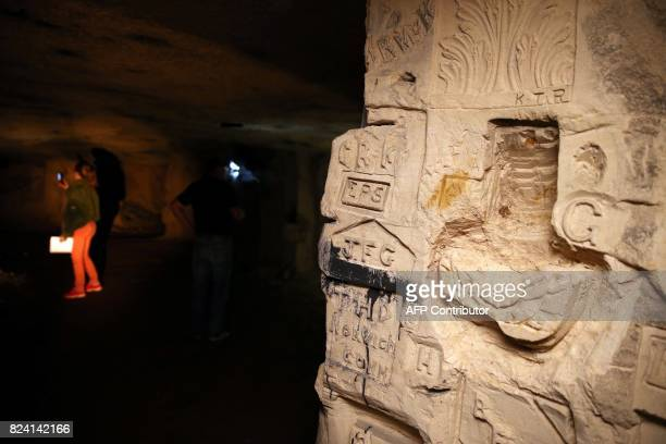 President of the Chemin des Dames Association Gilles Chauwin shows and explains to a visitor graffitis and basreliefs works realised in a cave...