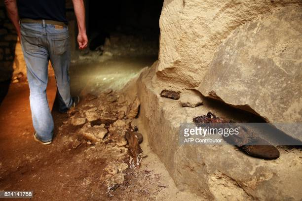 President of the Chemin des Dames Association Gilles Chauwin walks by soldiers' belongings in a cave successively occupied by French and German...
