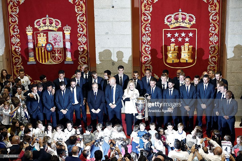 President of the Community of Madrid Cristina Cifuentes holds the trophy as she poses for a photograph with Real Madrid squad after Real Madrid won the UEFA Champions League Final match against Club Atletico de Madrid, at Madrid City Hall in Madrid, Spain on May 29, 2016.
