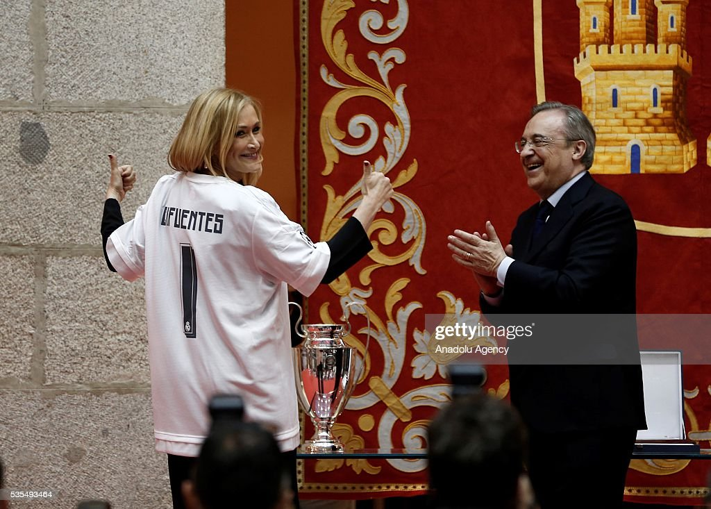 President of the Community of Madrid Cristina Cifuentes (L) poses for a photograph with a Real Madrid jersey with President of Real Madrid Florentino Perez (R) during their visit to President of the Community of Madrid Cristina Cifuentes after Real Madrid won the UEFA Champions League Final match against Club Atletico de Madrid, at Madrid City Hall in Madrid, Spain on May 29, 2016.