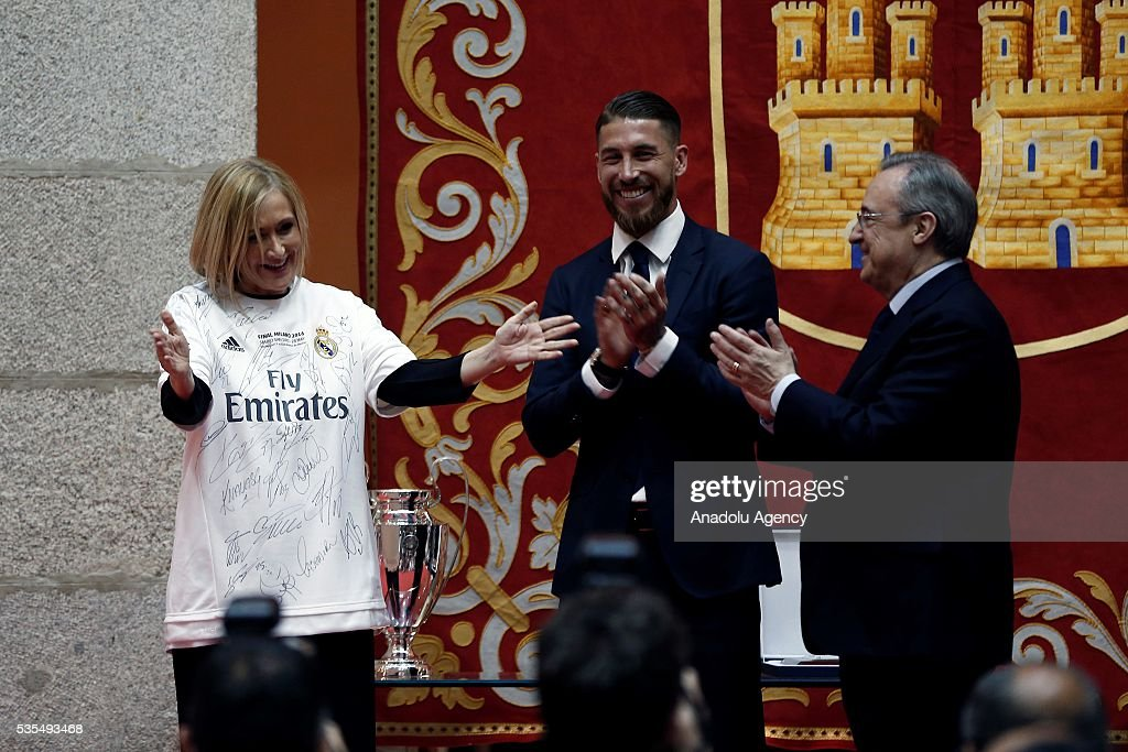 President of the Community of Madrid Cristina Cifuentes (L) poses for a photograph with a Real Madrid jersey with President of Real Madrid Florentino Perez (R) and Sergio Ramos during their visit to President of the Community of Madrid Cristina Cifuentes after Real Madrid won the UEFA Champions League Final match against Club Atletico de Madrid, at Madrid City Hall in Madrid, Spain on May 29, 2016.