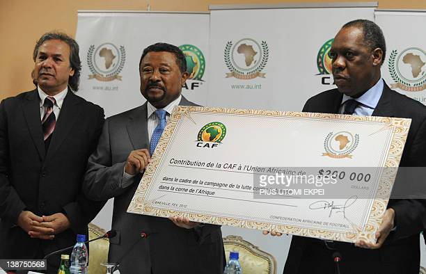 President of the Confederation of African Football Issa Hayatou presents a cheque of 200000 USD to President of African Union Commission Jean Ping...
