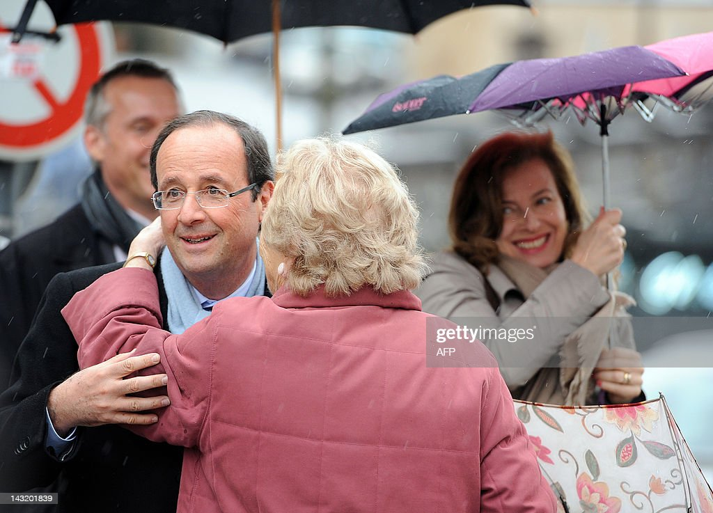 President of the Correze Council General Assembly Francois Hollande flanked by his companion Valerie Trierweiler is greeted by a woman during a visit...