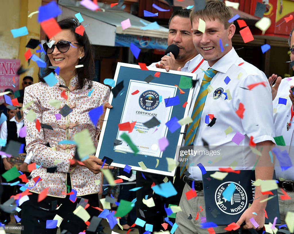 President of the Costa Rican Chinese Community, Isabel Yung (L), receives a Guinness record certificate from Guinness representative Ralph Hannah (R) in San Jose on February 12, 2013. The record was awarded for the largest fried rice, which was cooked by members of the Chinese community to celebrate the Chinese New Year. AFP PHOTO/Ezequiel BECERRA
